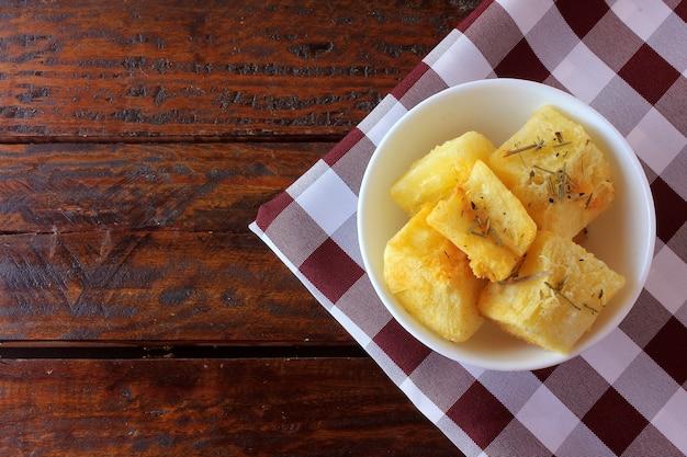 Gekookte en gebraden maniok (mandioca) in ceramische kom op rustieke houten lijst in restaurant