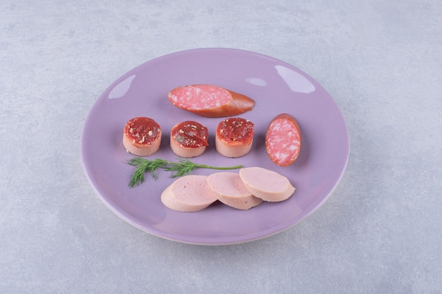 Gekookte en gerookte smakelijke worstjes op paarse plaat.