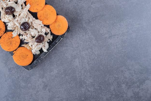 Gekookte en in blokjes gesneden kip met wortel op een houten bord.