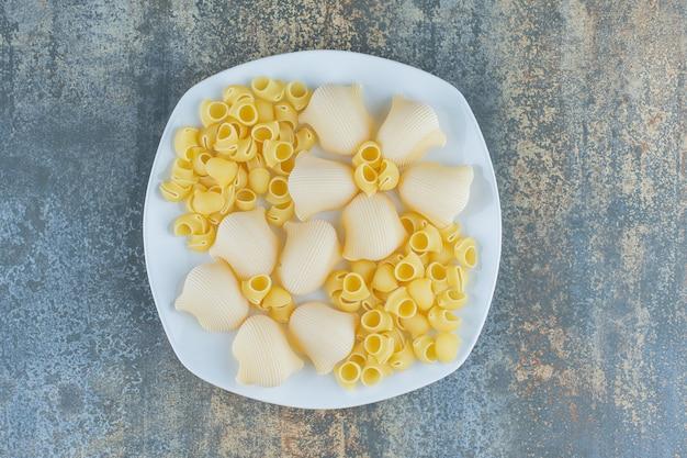 Gekookte en ongekookte pasta's in de kom, op het marmeren oppervlak.