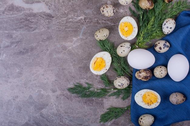 Gekookte en rauwe eieren op blauwe handdoek.