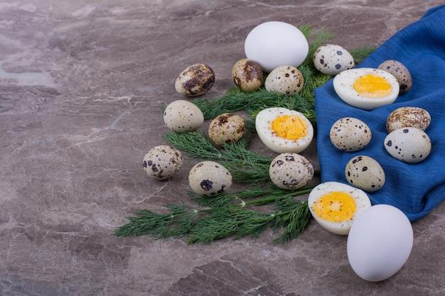 Gekookte en rauwe eieren op een stukje blauw weefsel.