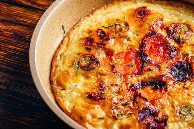 Gekookte frittata met chorizo, tomaten en chilipepers in een koekenpan over donkere houten tafel