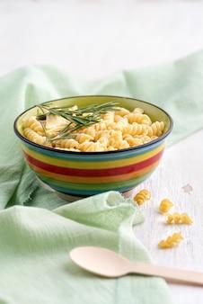 Gekookte fusilli pasta met rozemarijn in een plaat a op heldere tafel. close-up, het stilleven, selectieve aandacht. verticaal