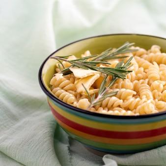Gekookte fusilli pasta met rozemarijn in een plaat a op heldere tafel. close-up, het stilleven, selectieve aandacht.