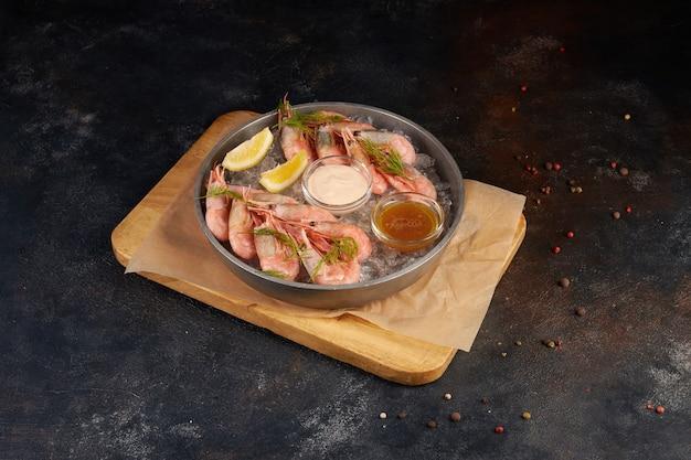 Gekookte garnalen, geserveerd met citroen en roomsaus