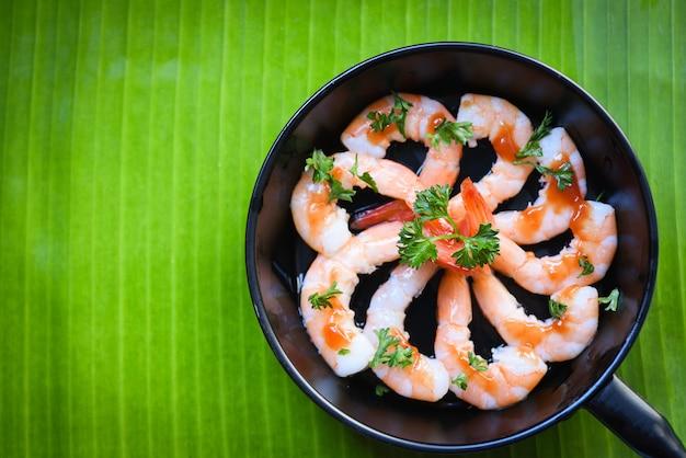 Gekookte garnalen van zeevruchtenplaat garnalen garneren op pan met sauskruiden en kruidenbanaanblad