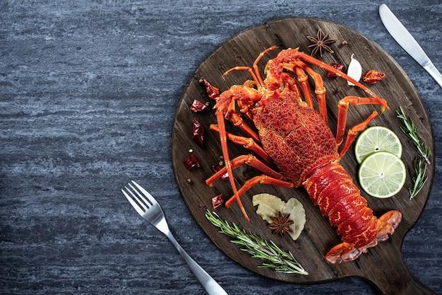 Gekookte gekookte kreeft, heerlijk diner zeevruchten maaltijd set met mes en vork op zwarte stenen leisteen achtergrond, restaurant menu ontwerp, bovenaanzicht, overhead