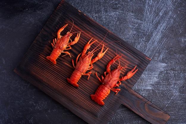 Gekookte gekookte rivierkreeftrivierkreeften klaar om op donkere houten achtergrond te eten. kopieer ruimte. overhead.