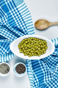 Gekookte groene erwten in een witte kom met kruiden, een lepel en een tafelkleed.