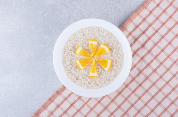 Gekookte havermout gegarneerd met stukjes sinaasappel op marmeren oppervlak