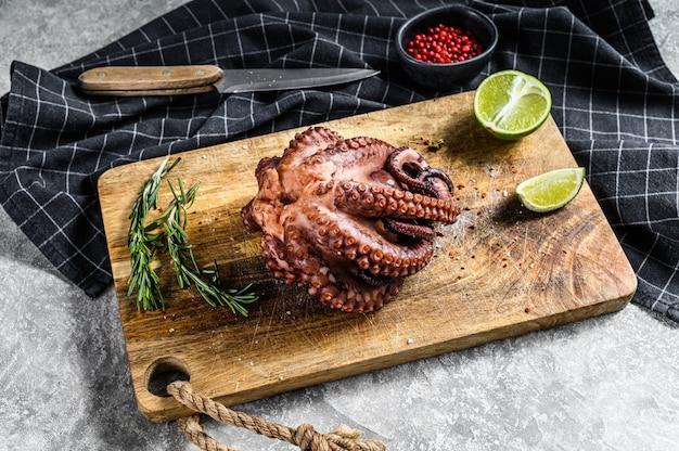 Gekookte hele octopus op een snijplank klaar om te snijden. grijs oppervlak. bovenaanzicht