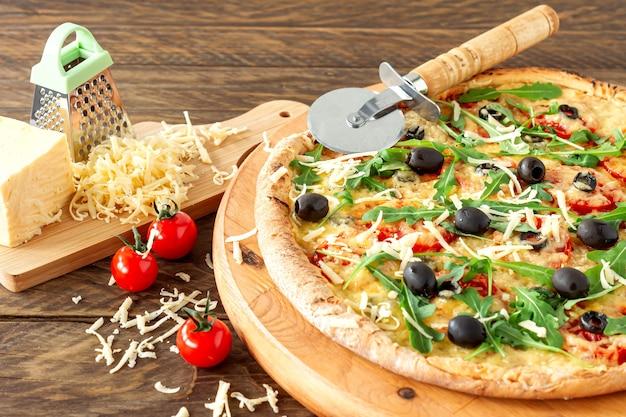 Gekookte hete pizzataart met pepperoni, tomaten, zwarte olijven, rucola en mozzarella op een houten bord.