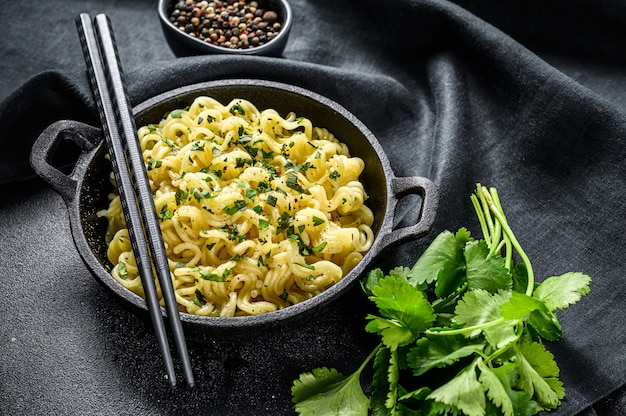 Gekookte instant noedels met sojavlees in een pot. vegetarisch gerecht. zwarte achtergrond. bovenaanzicht