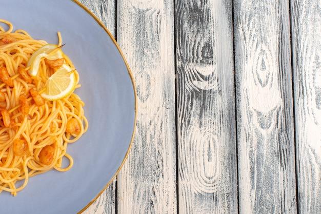 Gekookte italiaanse pasta lekker met plakjes citroen in blauw bord op grijs