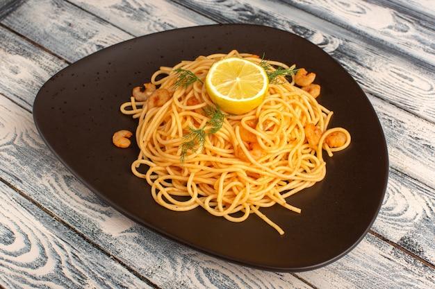 Gekookte italiaanse pasta met groene garnalen en citroen in bruine plaat op grijs