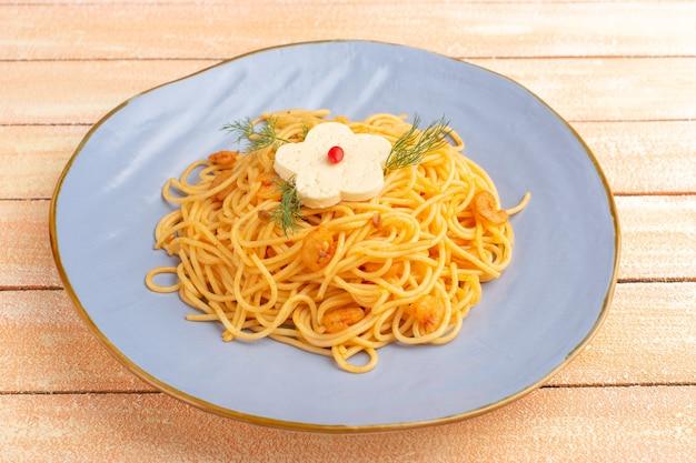 Gekookte italiaanse pasta smakelijke maaltijd met groenen binnen blauw bord op crème hout