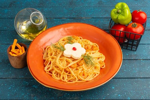 Gekookte italiaanse pasta smakelijke maaltijd met groenen binnen oranje plaat op blauw hout