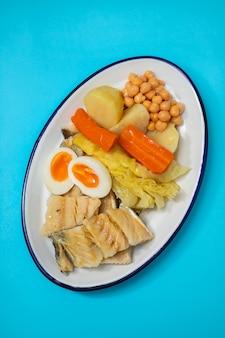 Gekookte kabeljauw met gekookte groenten en ei op witte schotel