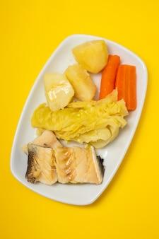 Gekookte kabeljauw met gekookte groenten op witte schotel