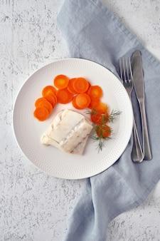 Gekookte kabeljauw met wortel en dille op witte plaat