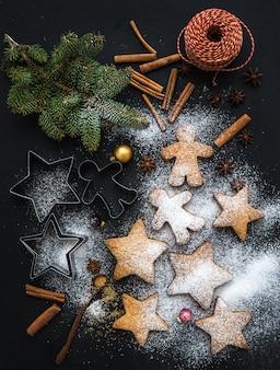 Gekookte kerstvakantie traditionele peperkoekkoekjes met suikerpoeder, anijs en kaneelstokjes