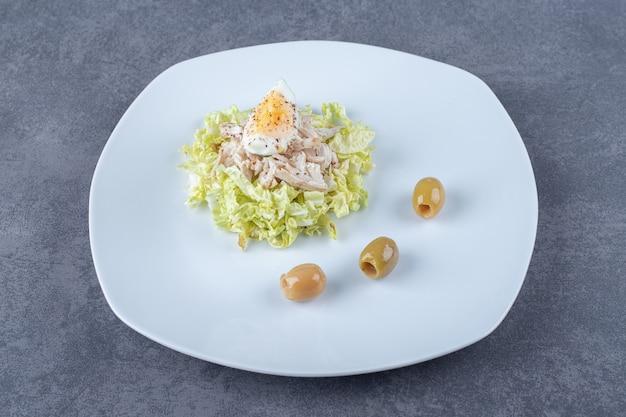 Gekookte kip en eiersalade op witte plaat.