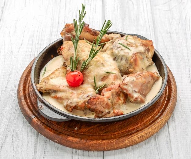 Gekookte kipfilet aangebraden in een gietijzeren koekenpan met romige pansaus
