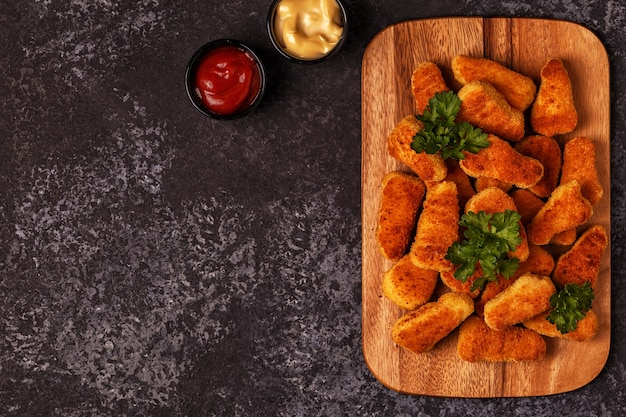 Gekookte kipnuggets op een bord met sauzen