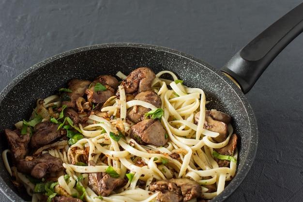 Gekookte kippenlever met ui en spaghetti op een kookpen met peterselie. lekker familiediner.