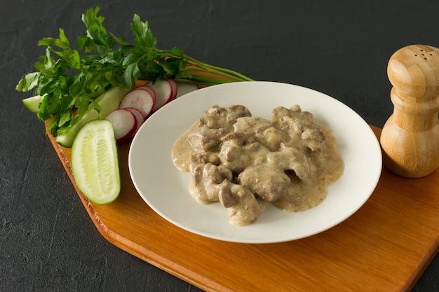 Gekookte kippenlever met ui en zure roomsaus op een bord geserveerd op houten bureau. rustieke stijl.