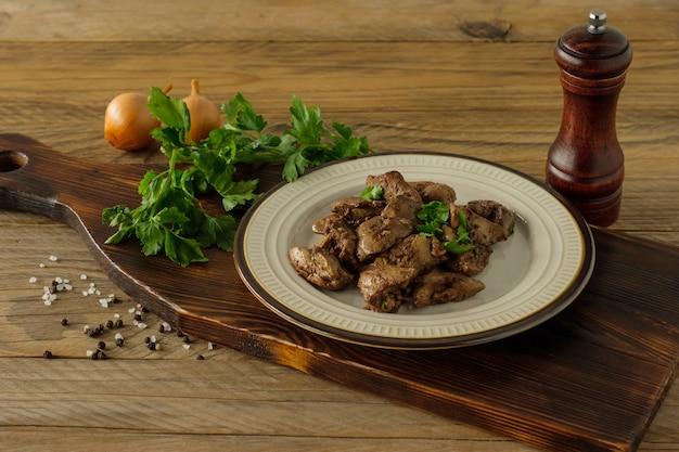 Gekookte kippenlever met ui op een bord geserveerd op houten bureau. rustieke stijl.