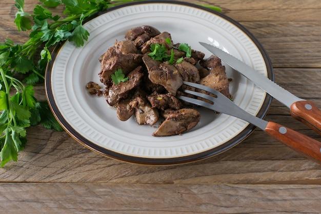 Gekookte kippenlever met ui op een bord geserveerd op houten bureau. rustieke stijl. Premium Foto