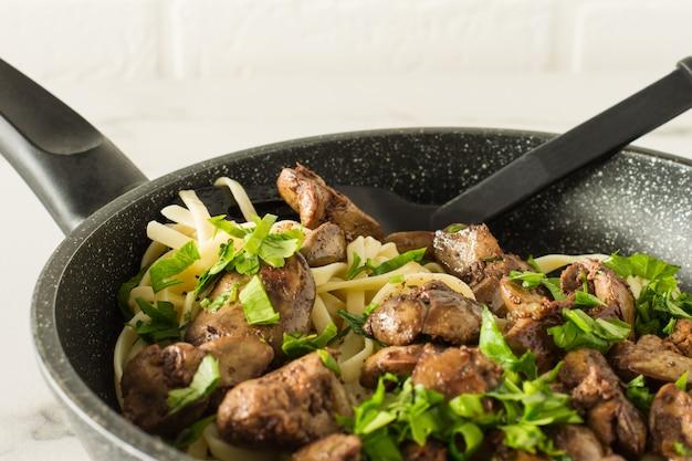 Gekookte kippenlever met ui op een kookpen op witte achtergrond.