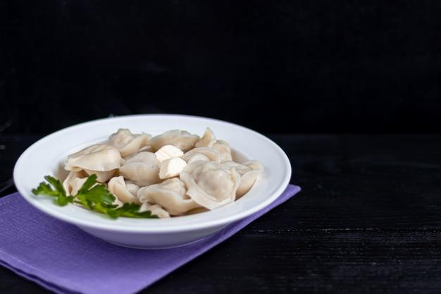 Gekookte knoedels met veren van groene uien.