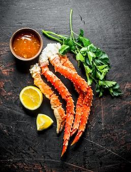 Gekookte krab met kruiden, saus en schijfjes citroen. op donkere rustieke achtergrond