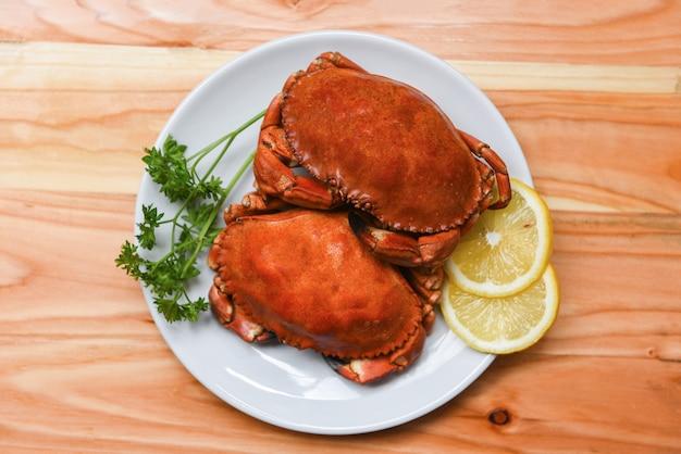 Gekookte krab op witte plaat met citroen, kruiden en specerijen zeevruchten gekookt rode stenen krabben salade