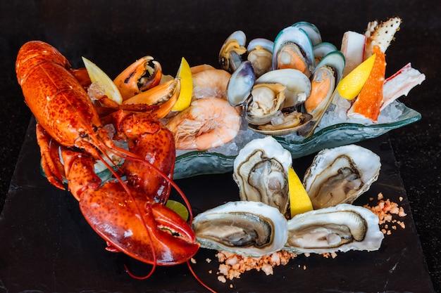 Gekookte kreeft, verse oesters, garnalen, mosselen en mosselen geserveerd in zwarte stenen plaat.
