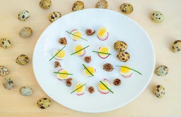 Gekookte kwarteleitjes met ansjovis en bieslook op een bord