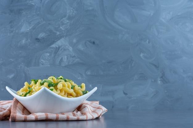 Gekookte macaroni met greens in witte kom.