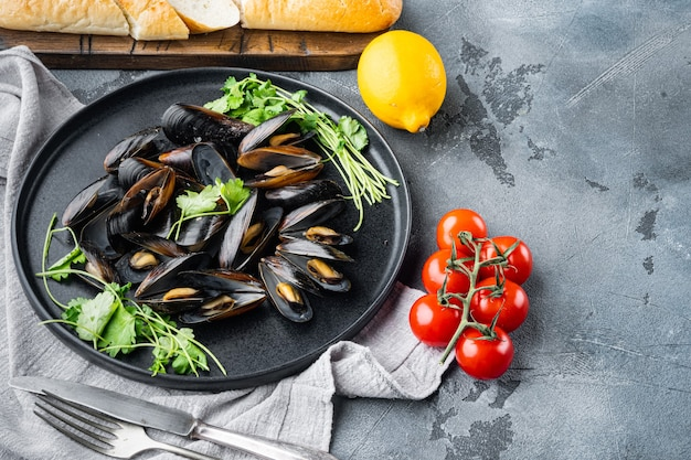 Gekookte mosselen in schelpen met kruiden en specerijen, op plaat, op grijze tafel