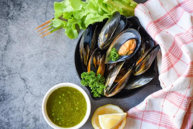 Gekookte mosselen met kruiden citroen en donkere plaat achtergrond - verse zeevruchten schelpdieren op kom en pittige saus salade in het restaurant mossel schelp voedsel