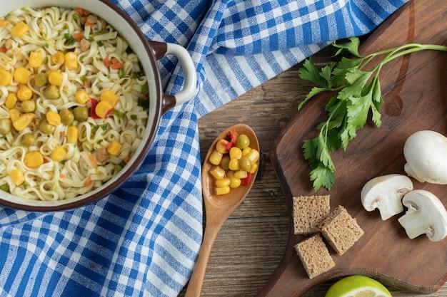 Gekookte noedels met erwten en likdoorns en verse groenten op een houten bord