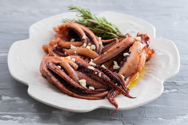 Gekookte octopus met knoflook op witte plaat