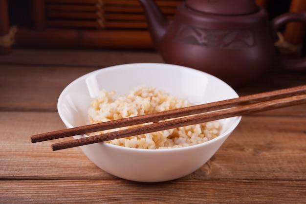 Gekookte ongepelde rijst in witte kom met eetstokjes op de houten achtergrond.