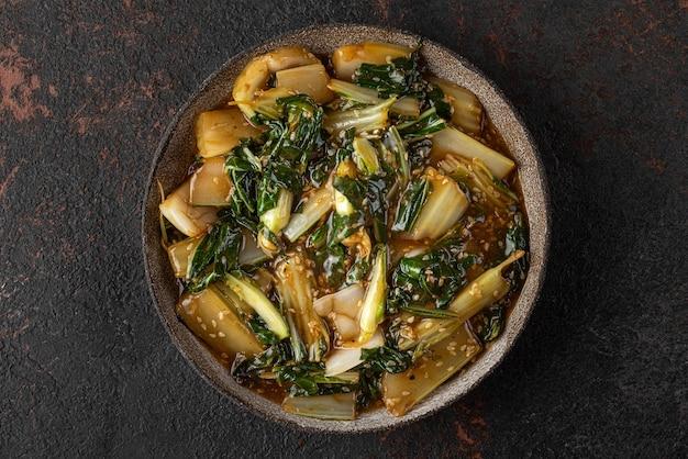 Gekookte paksoi of chinese kool met sesamzaadjes en sojasaus op donkere achtergrond. aziatisch chinees eten. bovenaanzicht. gezond veganistisch of vegetarisch eten