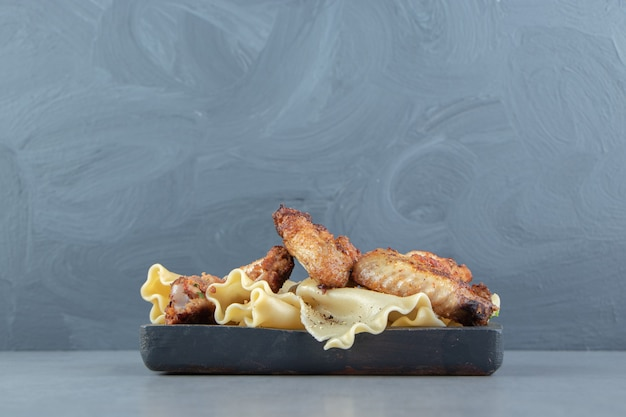 Gekookte pasta en gegrilde kip op zwarte plaat.