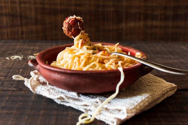 Gekookte pasta en gehaktbal in het aardewerk