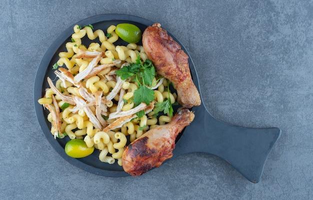 Gekookte pasta en kippenpoten op een zwart bord.