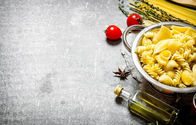 Gekookte pasta in de pan met olijfolie en tomaten op de stenen tafel